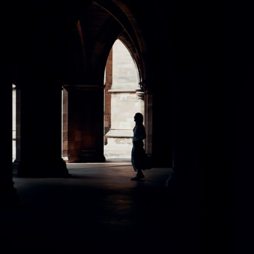 A person stands in the shadows of the arches on the University of Glasgow campus