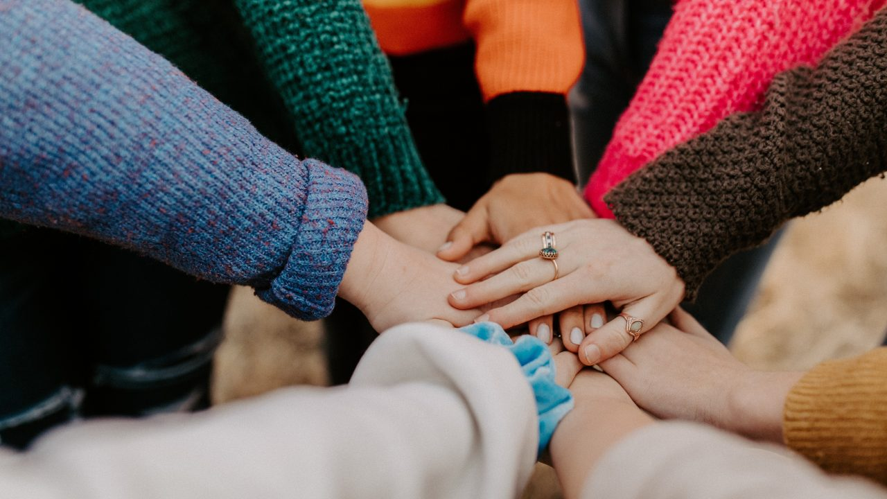 People gathered in a circle, placing their hands on top of one another.
